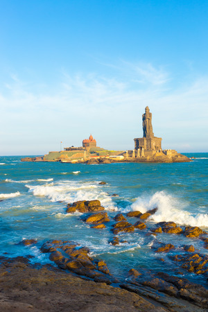 neighboring: Vivekananda Rock is home to a memorial and neighboring island Thiruvalluvar Statue off the coast of Kanyakumari, Tamil Nadu, India on a blue sky day. Vertical Stock Photo
