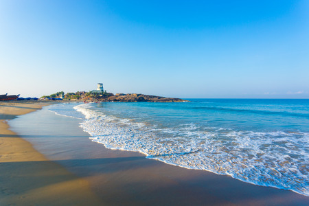 kovalam: The life guard aid post resembling a stubby lighthouse sits atop a rocky outcrop on the tourist town of Kovalam Beach in the morning in Kerala, India. Horizontal Stock Photo
