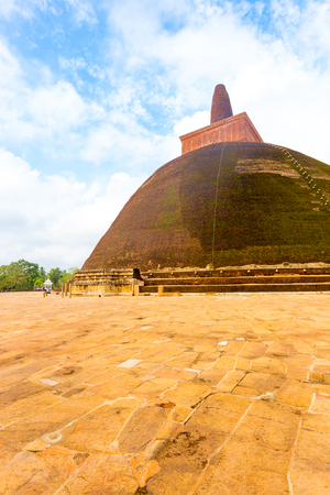 dagoba: Massive Abhayagiri dagoba or stupa stands atop masonry base with intact spire in the ancient capitol of Anuradhapura Kingdom on a cloudy, blue sky day in Sri Lanka. Copy space Stock Photo