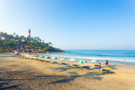 light house: Kovalam, India - March 1, 2015: Beach chairs and parasols line the beachfront on the sand in view of ocean waves at Kovalam Light House Beach in Kerala Editorial