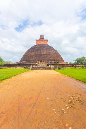 dagoba: Dirt road leading to centered Jetavanaramaya Dagoba or stupa ruins on a beautiful blue sky day in ancient capitol of Anuradhapura Kingdom in Sri Lanka. Vertical