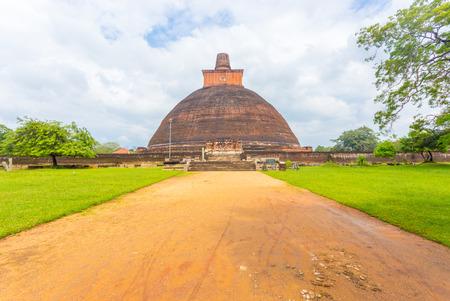 dagoba: Dirt road leading to centered Jetavanaramaya Dagoba or stupa ruins on a beautiful blue sky day in ancient capitol of Anuradhapura Kingdom in Sri Lanka. Horizontal