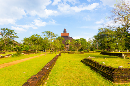 Wall remains from former structures in grass lead viewer to large Jetavanaramaya Stupa and its broken spire at ancient Anuradhapura capitol ruins in Sri Lanka. Horizontal