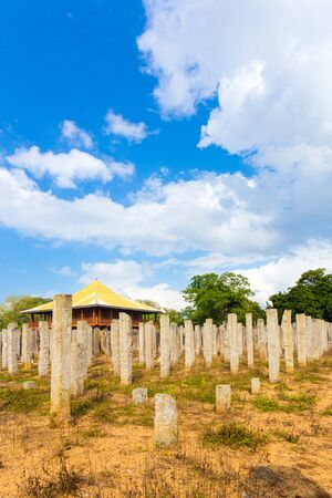 Upright original stone pillars are all that remain of the ruins of the Brazen Palace or Lovamahapaya on a cloudy blue sky day in ancient Anuradhapura capitol in Sri Lanka. Vertical