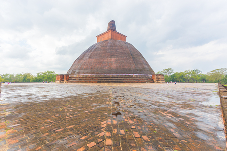 dagoba: Jetavanaramaya Dagoba or stupa ruins with damaged spire seen centered from wet platform corner in the ancient capitol of Anuradhapura Kingdom on a cloudy day in Sri Lanka