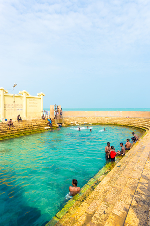 Keerimalai, Sri Lanka - February 5, 2015:  Sri Lankan swimmers enjoy the sacred Keerimalai Hot Springs with an ocean view, a tourist attraction on the northern coast of Jaffna. Vertical Editorial