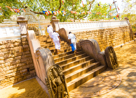 anuradhapura: Anuradhapura, Sri Lanka - February 7, 2015: People walking past carved moonstone at base of steps to Jaya Sri Maha Bodhi containing the sacred fig tree of Budda enlightenment in ancient capitol