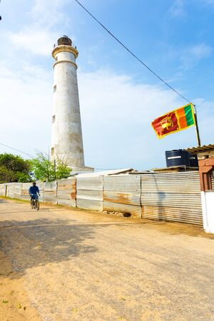 Point Pedro, Sri Lanka - February 4, 2015: A bicyclist riding on road next to Point Pedro Lighthouse, a landmark now occupied by the military on the northern coast of Jaffna