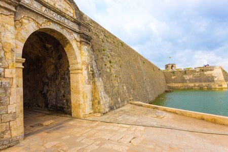 Jaffna Fort entrance and wall bordered by watery moat in Sri Lanka. Angled