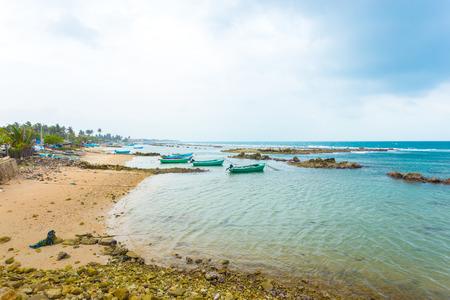 beachfront: Fishing boats anchored outside a fishermen village in Point Pedro on a stormy day along the northern coast of Jaffna, Sri Lanka. Horizontal Stock Photo