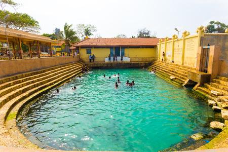 Keerimalai, Sri Lanka - February 5, 2015:  Sri Lankan people swimming in the Keerimalai Hot Springs, a tourist attraction on the northern coast of Jaffna. Horizontal