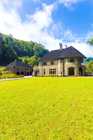 casa colonial: Un jardín plantado en una colina detrás del bungalow principal en el monasterio de Adisham Saint Benedict, un monumento turístico, en un día de cielo azul en Haputale, Sri Lanka. Vertical Foto de archivo