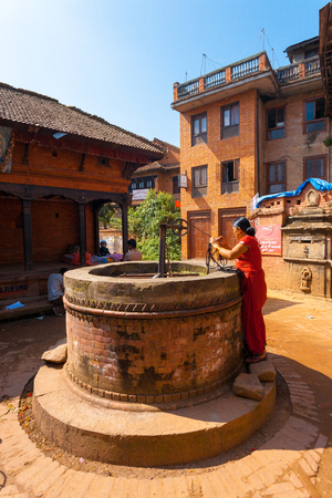 well: Bhaktapur, Nepal - October 25, 2013: Nepalese woman pulling water from traditional community ground well