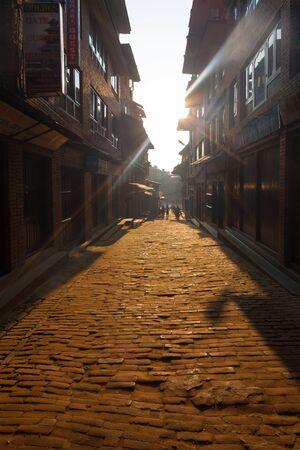 lightbeam: Bhaktapur, Nepal - October 31, 2013: Sun rays shoot down brick cobblestone road among alleys around historic Bhaktapur Durbar Square at morning time. Before 2015 earthquake damage