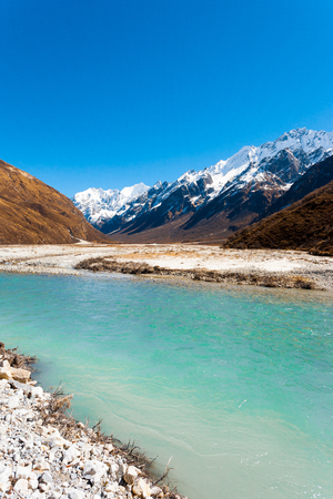 Colorful glacial river water at high elevation flowing thru Langtang Valley with Gangchenpo mountain peak background, part of Himalayan range in Nepal Stock Photo