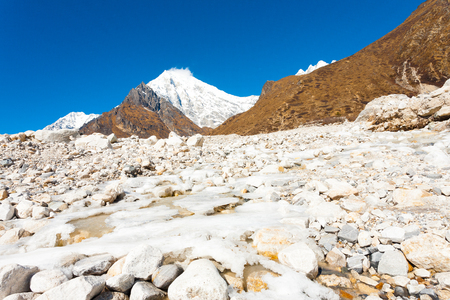 Icy alpine river running through white rocky terrain landscape at high elevation alpine tundra with Langtang Lirung peak background near Kyanjin Gompa village, Nepal. Horizontal