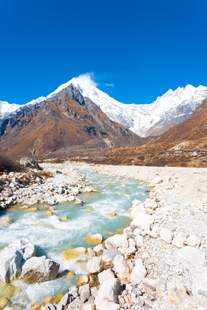 Rocky barren terrain landscape lines a fast flowing glacier water river with Himalayan mountain range, Langtang Lirung peak, in background at high altitude in Nepal Stock Photo