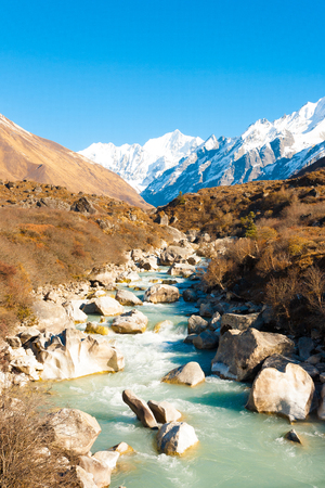 Landscape view of river running through Langtang valley with view of snow-capped Himalayan mountain range background and Gangchenpo Peak in Nepal