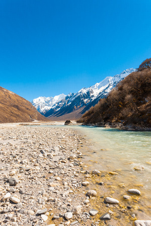 Langtang valley at high elevation with flowing glacial river water from Himalayan mountain range and snow-capped Gangchenpo peak in background in Nepal. Vertical