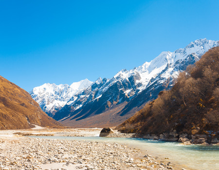 Langtang valley at high altitude with flowing glacial river water leading to Himalayan mountain range and snow-capped Gangchenpo peak in background in Nepal. Horizontal Banque d'images