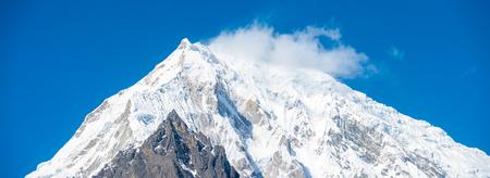 Closeup of snow-capped, windswept Langtang Lirung mountain peak, part of Himalayan range in Nepal. Horizontal Stock Photo