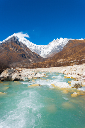 Landscape view of Langtang Lirung peak, part of snow-capped Himalaya Mountain range behind fast flowing glacial water river at high altitude in Nepal. Vertical
