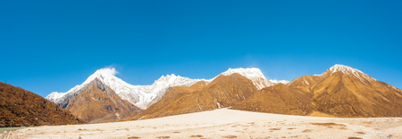 Panoramic landscape view of snow capped Himalayan mountain range and Langtang Lirung peak with barren valley at alpine tundra high altitude near Kyanjin Gompa in Nepal Stock Photo