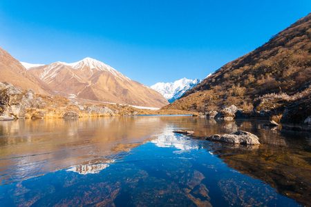 Thin layer of ice on a clear water, high altitude pond reflects snow-capped Gangchenpo Peak, part of the Langtang Himalayan Mountain range in Nepal. Horizontal