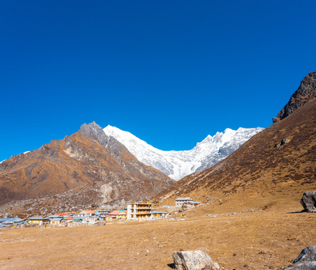 Majestic view of snow-capped Langtang Lirung Himalayan mountain range with Kyanjin Gompa village in foreground in Nepal. Before 2015 Gorkha earthquake damage. Horizontal Stock Photo