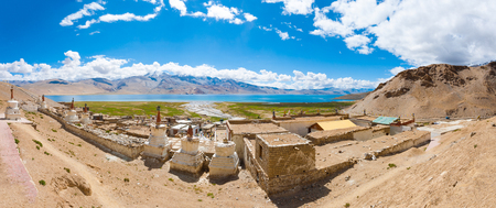 Panoramic view of Tso Moriri Lake from hill behind Korzok village houses and Tibetan stupas on a blue sky summer day in Ladakh, India