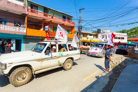 Pokhara, Nepal - May 11, 2017: Communist Party supporters waving Maoist flags and campaigning for the 2017 national elections