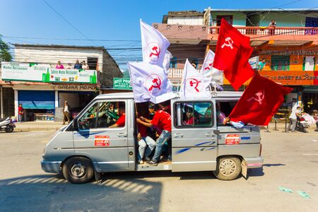Pokhara, Nepal - May 11, 2017: Maoist Communist Party members waving flags attached to vans during campaign for the 2017 national elections