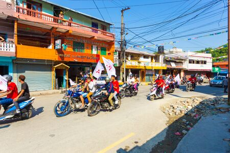 Pokhara, Nepal - May 11, 2017: Maoist Communist Party supporters waving flags and riding motorcycles during campaign for the 2017 national elections