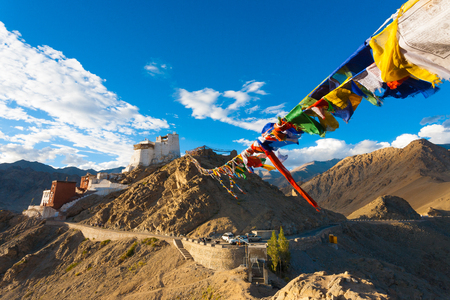 Tibetan prayer flags lead to Tsemo Fort and Namgyal Tsemo Monastery atop a mountain above Leh on a clear summer day in Ladakh, India
