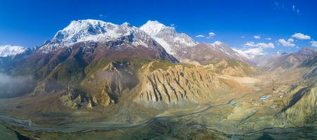 標高の高い山脈とネパールの下谷マナン村雪をかぶったヒマラヤのアンナプルナのパノラマが一望