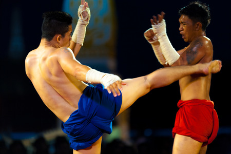 Bangkok, Thailand - April 10, 2007: Muay Thai kickboxer with wrapped hands kicking a wincing opponent during traditional exhibition kickboxing match at the Grand Palace