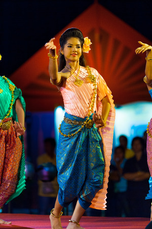 thai dancing: Bangkok, Thailand - April 10, 2007: Beautiful female Thai dancer in traditional clothes performing on stage at night exhibition in front of the Grand Palace