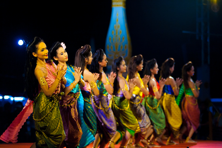 Bangkok, Thailand - April 10, 2007: Row of female Thai dancers in colorful traditional clothes performing on stage at a night exhibition in front of the Grand Palace Editorial