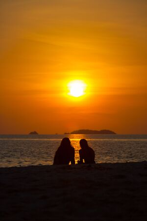 Two unidentifiable people watch a setting sun into the ocean on a sand beach by the ocean in front of bright orange sky