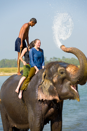 Chitwan, Nepal - December 5, 2007: Two female tourists getting splashed with trunk water on an elephant ride in the river at Chitwan National Park Editorial