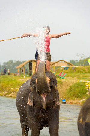 Chitwan, Nepal - December 4, 2007: A female tourist in red enjoying getting splashed by elephant trunk during elephant ride at Chitwan National Park Editorial