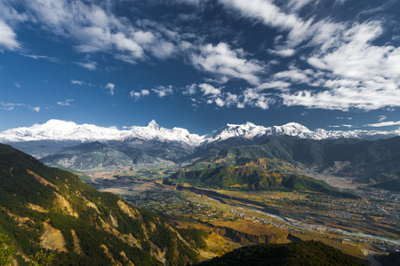 Stylized landscape view of snow capped Annapurna Himalayan Mountain range and valley below on a blue sky day near Pokhara, Nepal Stock Photo
