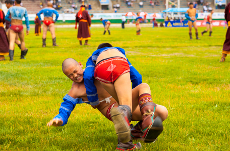 Ulaanbaatar, Mongolia - June 11, 2007: A young boy wrestler is thrown to the ground at wrestling match inside the National Sports Stadium at the Naadam Festival Editorial