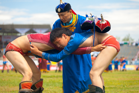 Ulaanbaatar, Mongolia - June 11, 2007: A referee checking two young wrestlers inside the National Sports Stadium at the Naadam Festival wrestling competition Editorial