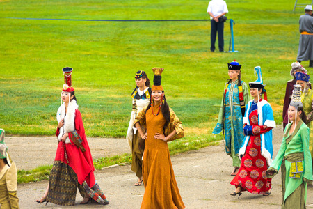 Ulaanbaatar, Mongolia - June 11, 2007: Beautiful Mongolian women dressed in variety of traditional national costume walking in the opening ceremony of the Naadam Festival