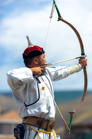 Ulaanbaatar, Mongolia - June 11, 2007: Male archer in traditional garb pulling bowstring and aiming arrow with concentration at the Naadam Festival archery outdoor event