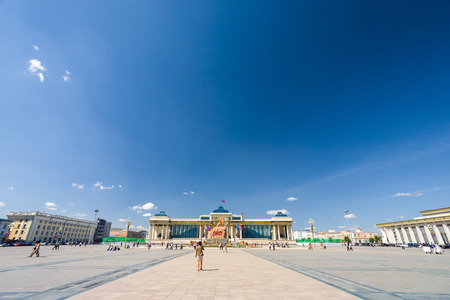People walking around Sukhbaatar or Chinggis Square under wide blue sky on a  summer day in Ulaanbaatar, Mongolia Stock fotó