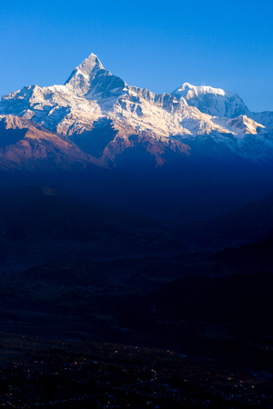 Snow capped top of Machapuchare Fishtail Himalayan mountain lighted by early morning dawn sunlight with dark valley below Sarangkot, Nepal