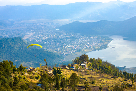 High angle aerial view of paraglider descending onto Pokhara and Phewa Lake seen from Sarangkot, Nepal