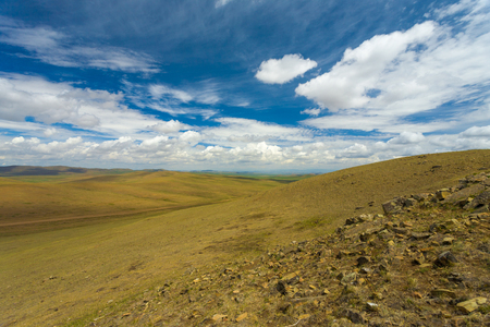 Grassy, hilly terrain on the Mongolian steppe in the countryside of Mongolia